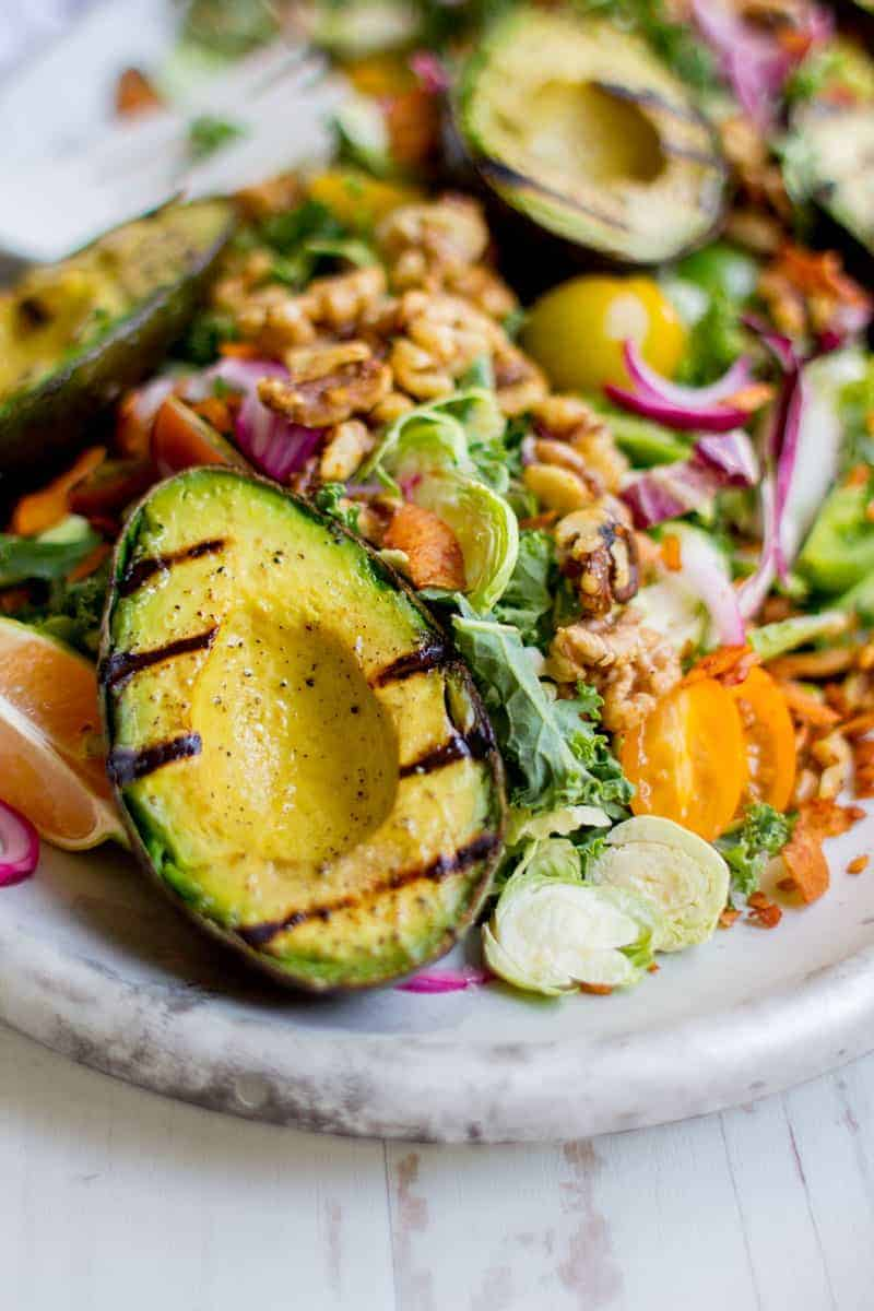 Grilled avocado on a white platter with sliced Brussels sprouts, halved cherry tomatoes, walnuts, and shaved red onion.