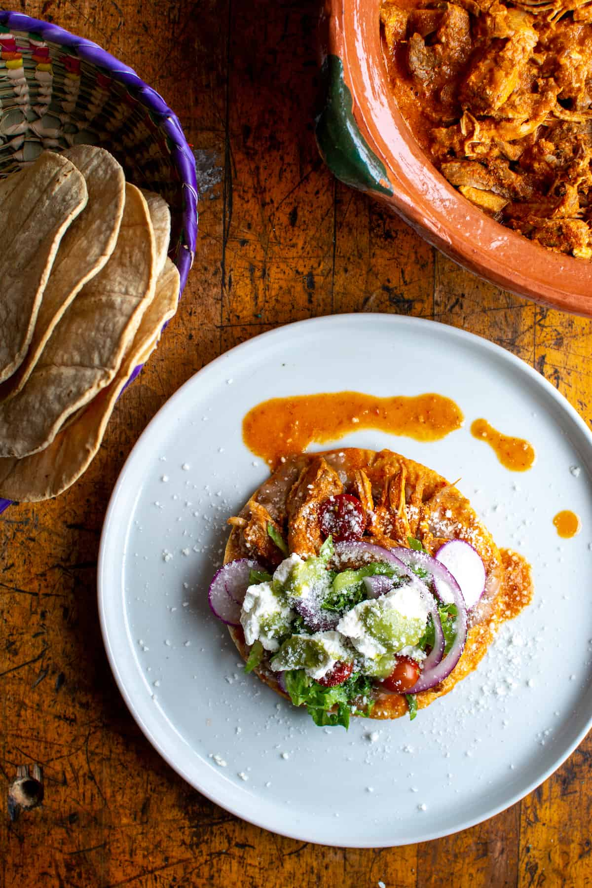 A pork tostada sitting on a white plate with a basket of tostadas next to it and a ceramic dish filled with braised pork.