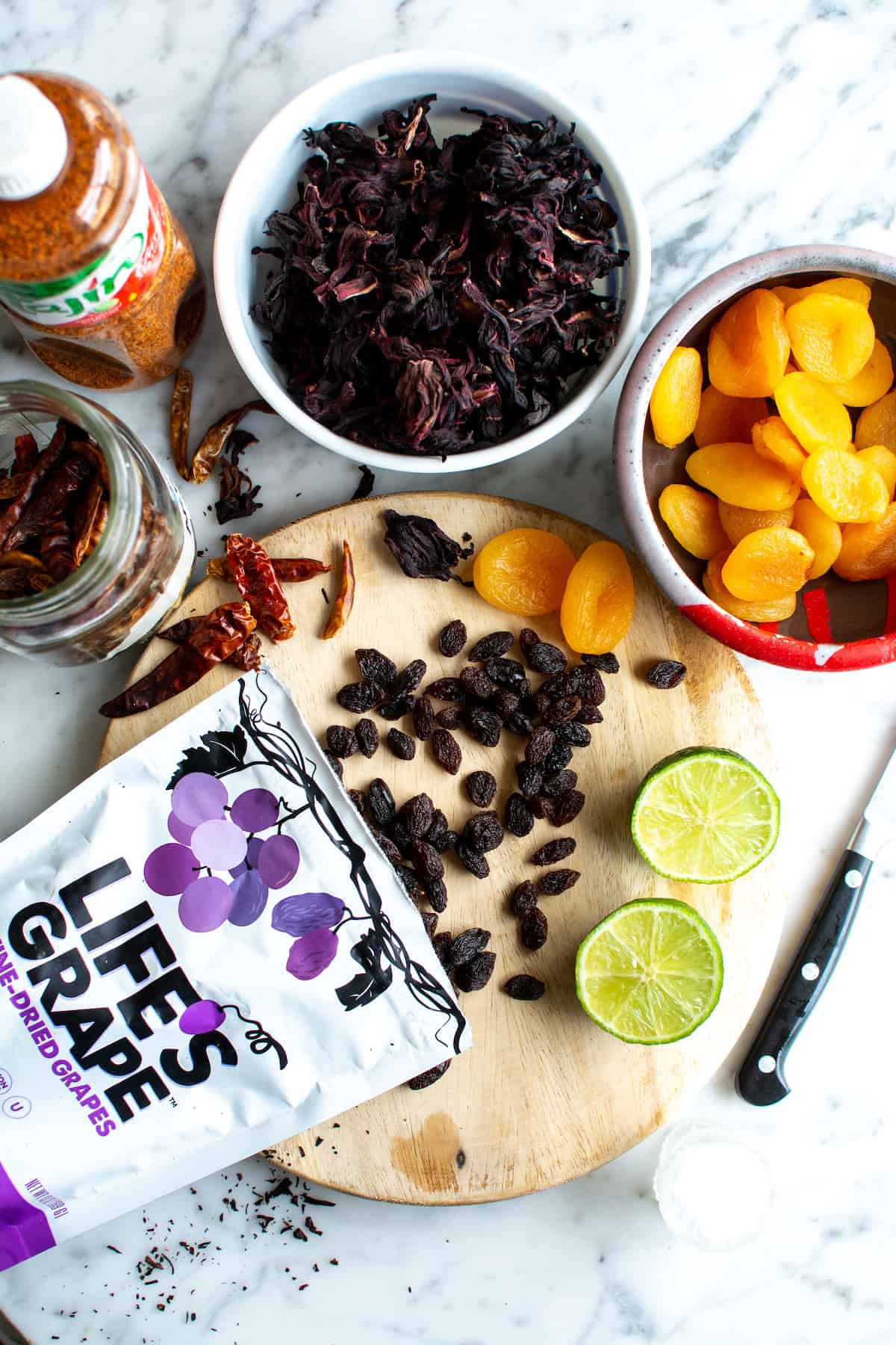 Ingredients to make chamoy on a marble table, a package of grapes, jamaica, apricots, lime, arbol chiles, and Tajin.