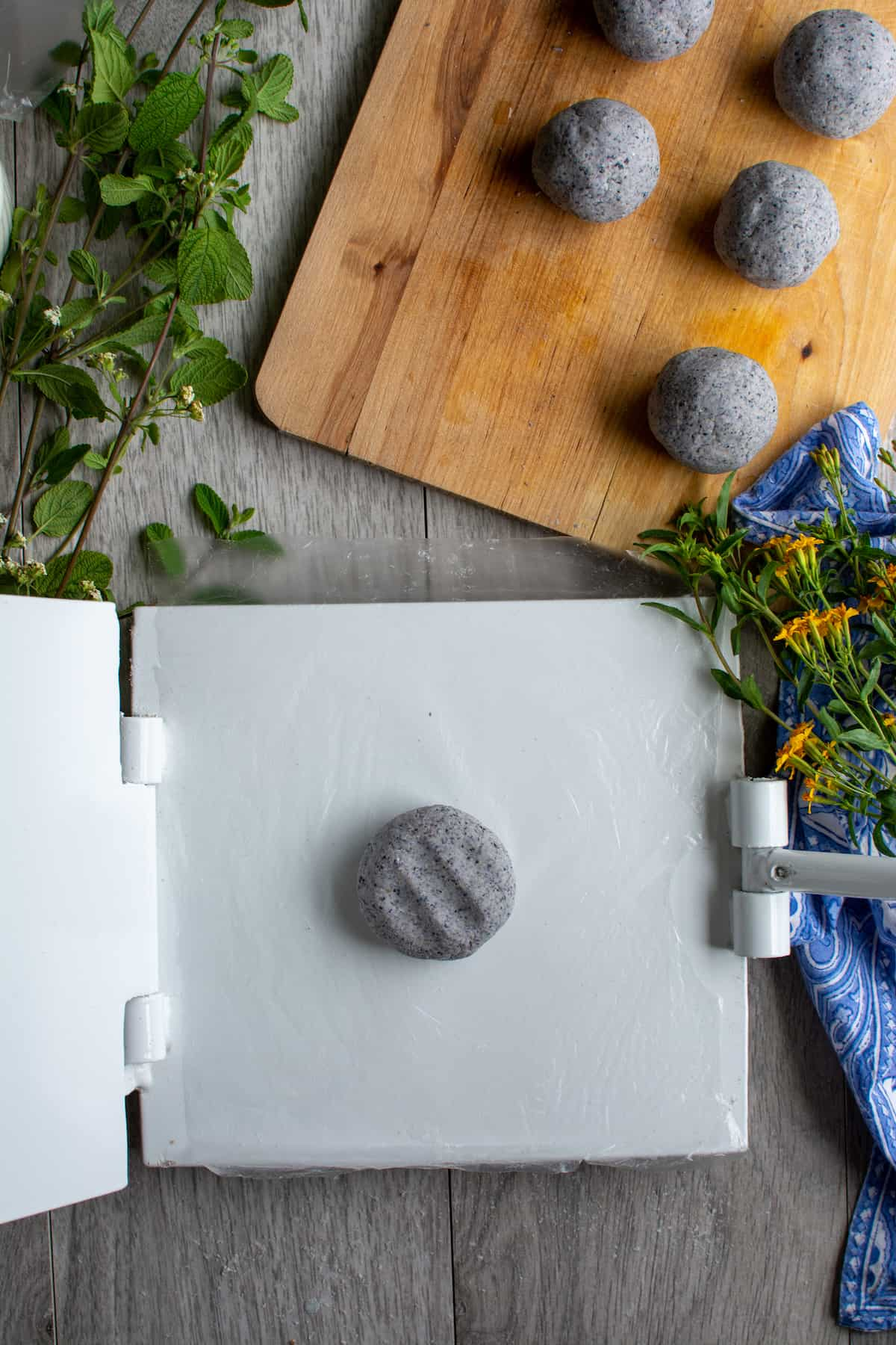 A flattened ball of masa dough on a white tortilla press with several other balls of blue corn masa on a wood cutting board next to it.