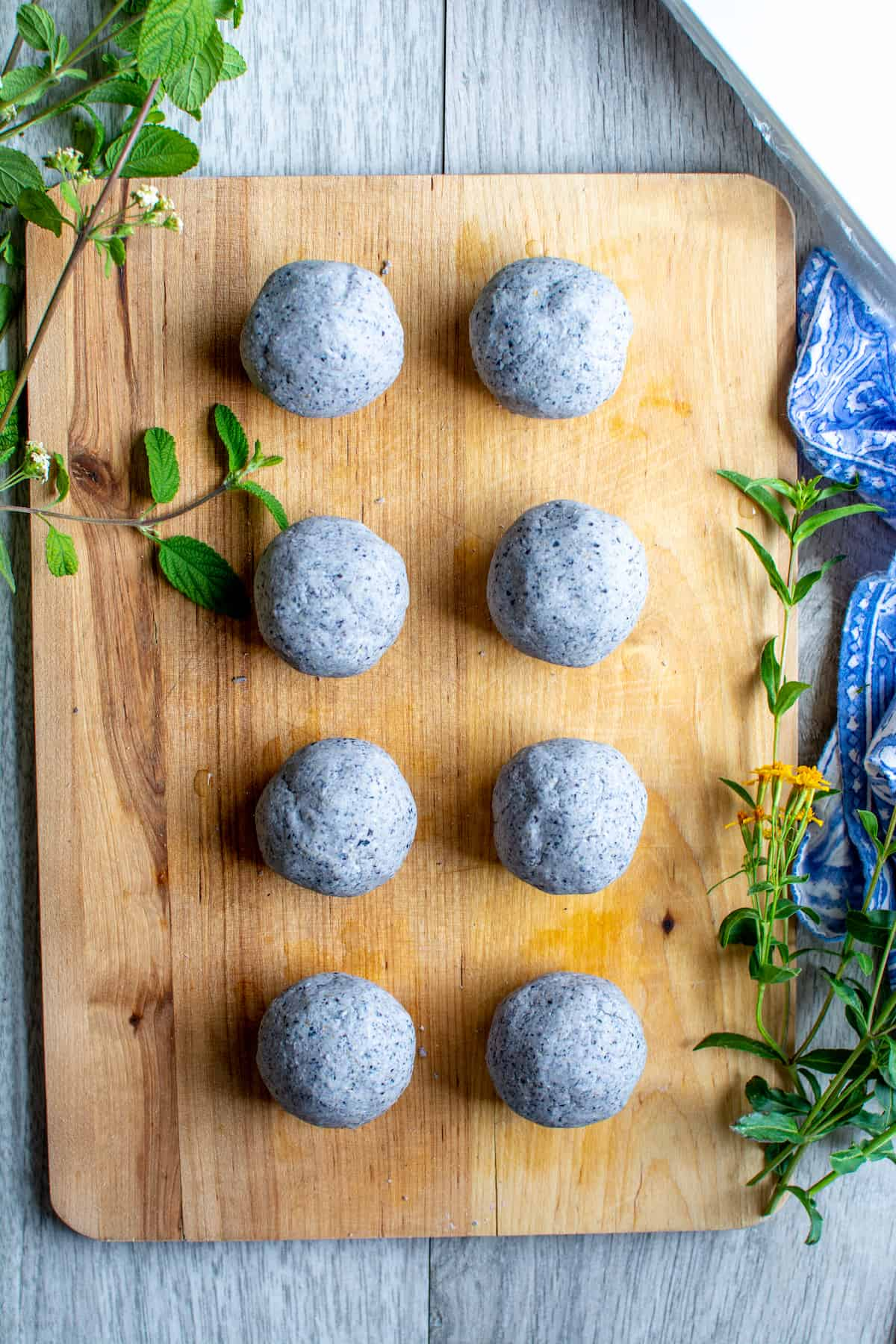 8 balls of blue corn masa dough sitting on a wood cutting board surrounded by sprigs of Mexican oregano and tarragon.