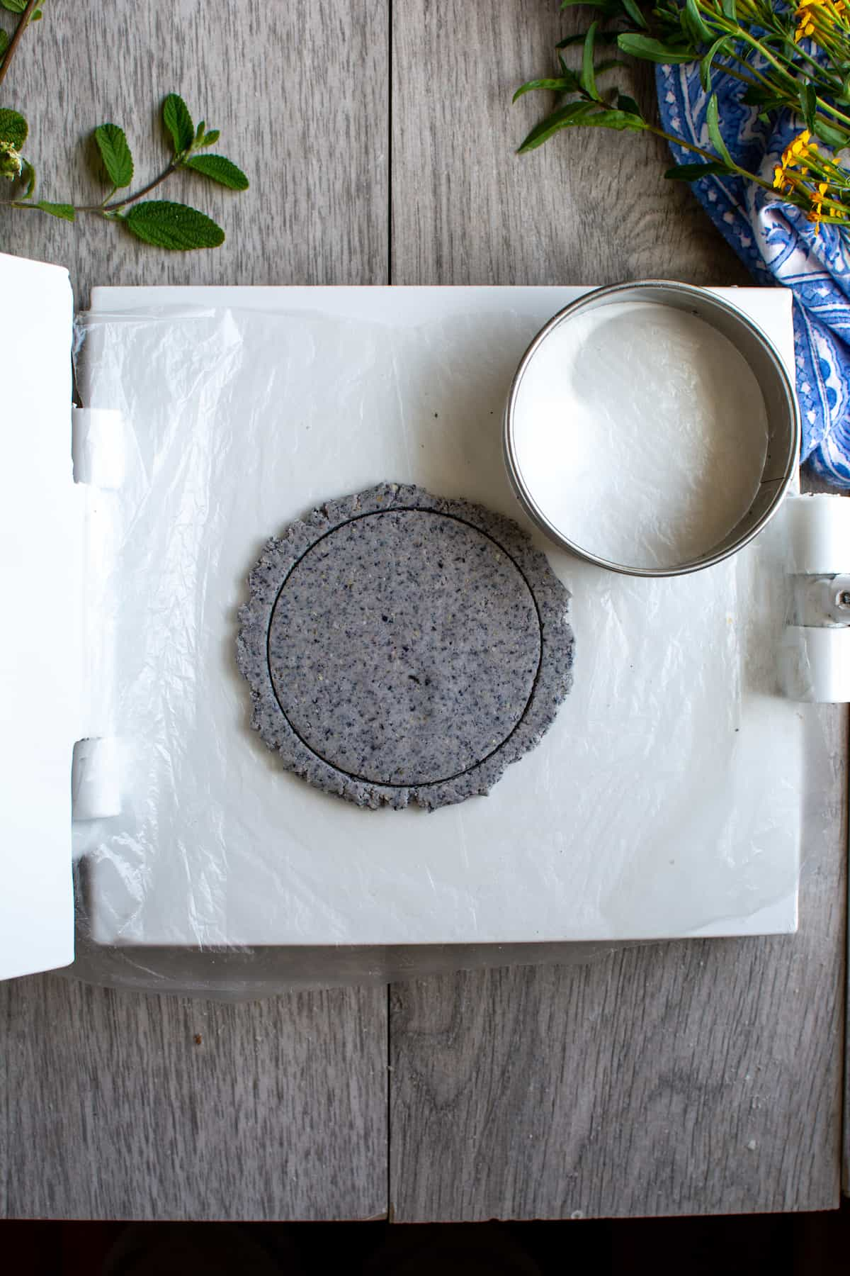 A flattened round of blue corn masa dough cut with a round metal biscuit cutter which is sitting next to it on a white tortilla press.