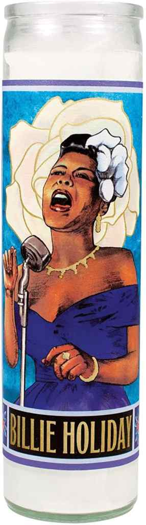 A Billie Holiday saint candle with an image of Billie Holiday singing and a white flower behind her on the candle.
