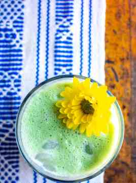 A glass of green Matcha Horchata with a yellow flower in the glass. The glass is sitting on a blue and white runner on a wood table.
