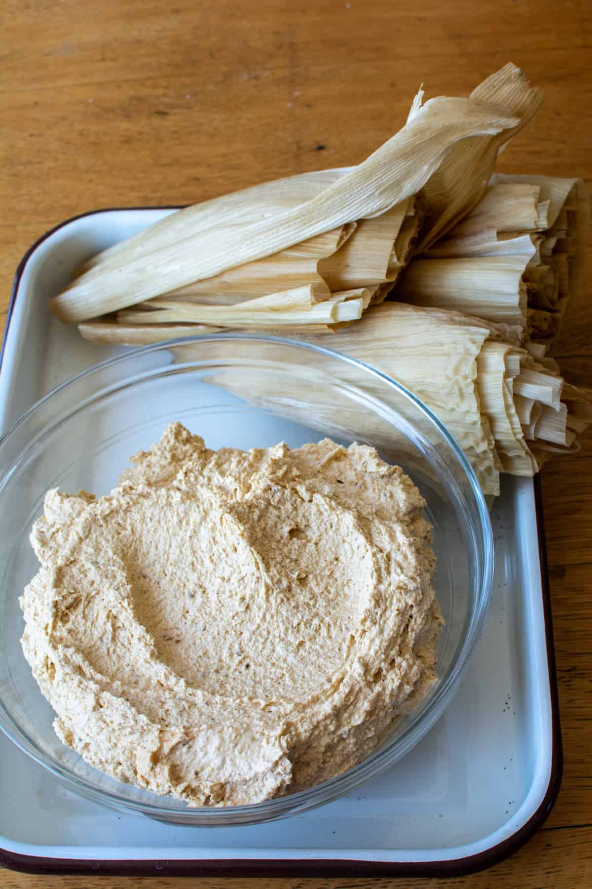 A glass bowl filled with masa dough sitting in a white tray with a stack of soaked corn husks behind it.