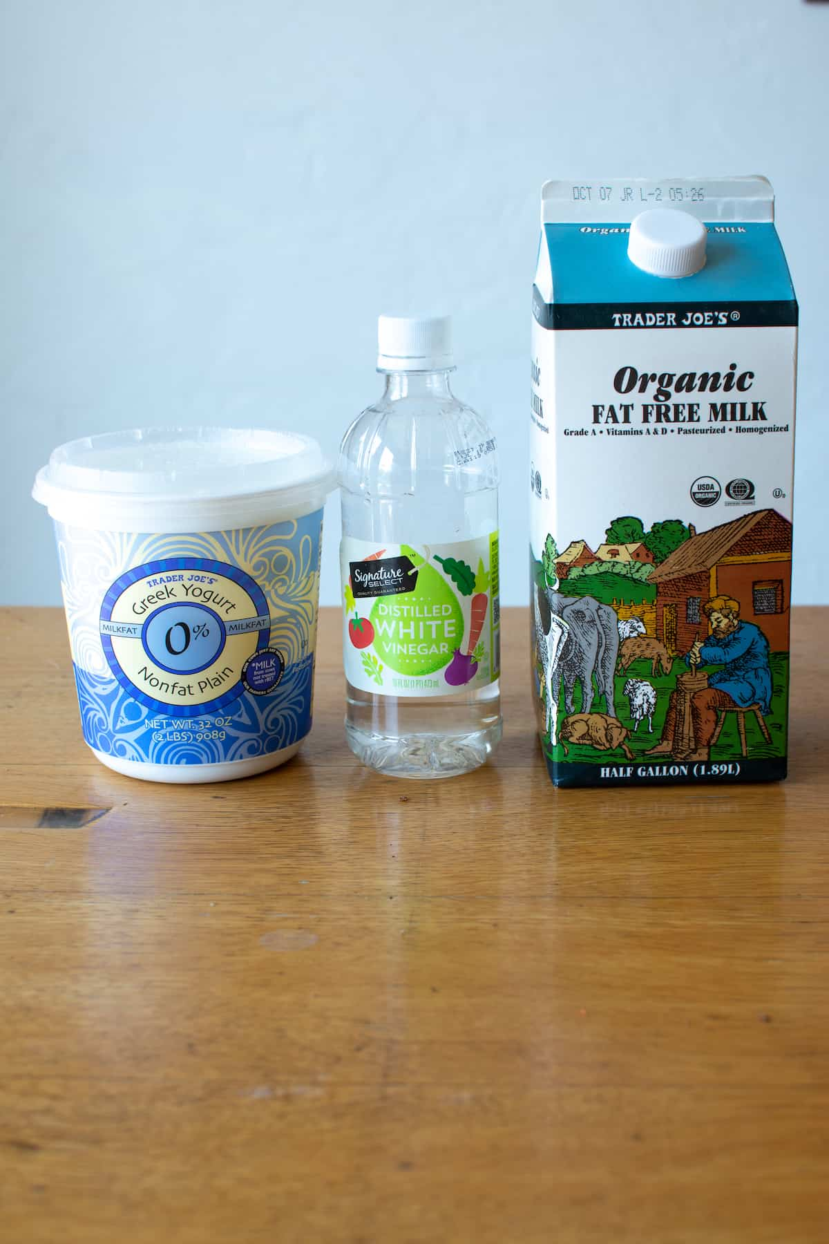 The ingredients needed to make Panela cheese: Greek yogurt, distilled white vinegar, and non-fat milk sitting on a wood table.