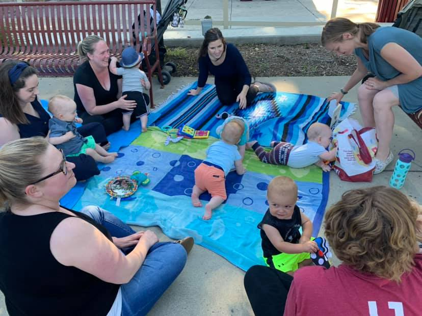 Moms and babies gathered outside around blanket