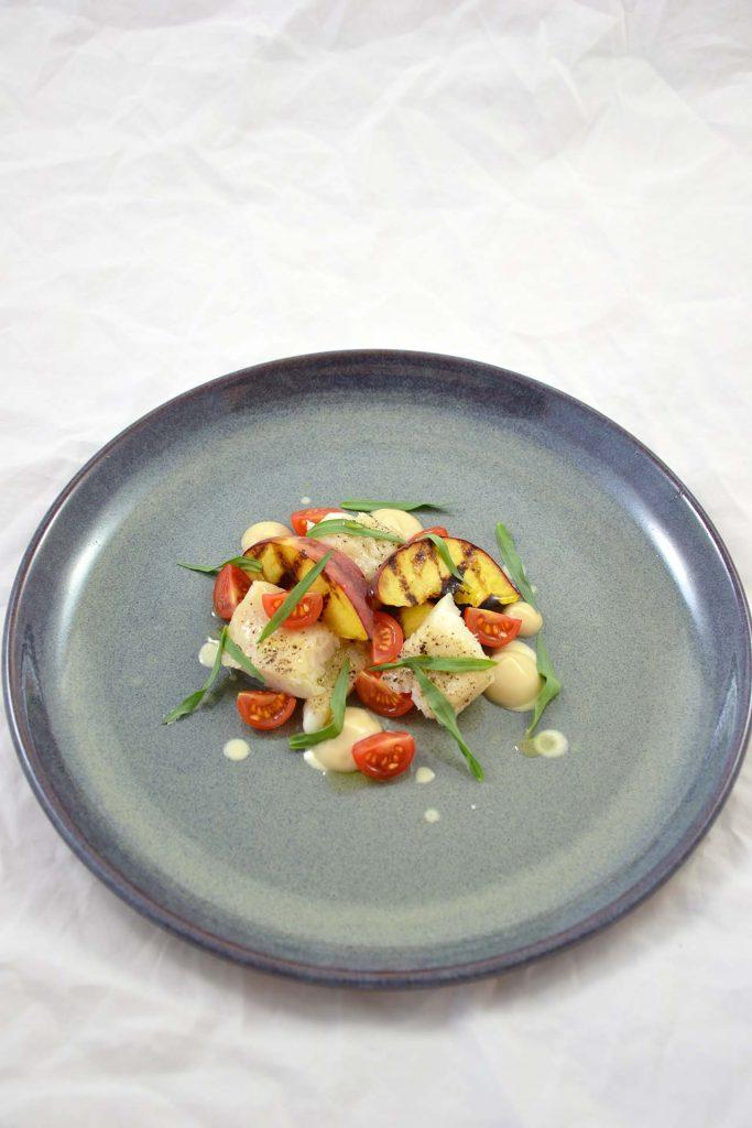 Heilbutt mit gegrilltem Pfirsich, Geflügelgel, Tomate, Ayran und Estragon.