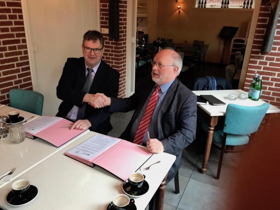 Wethouder Theo Groot en Hoogheemraad Rob Veenman schudden elkaar de hand na het ondertekenen van de overeenkomst.