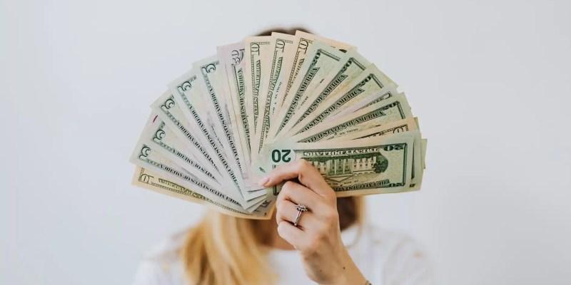 woman holding fan of us dollar bills