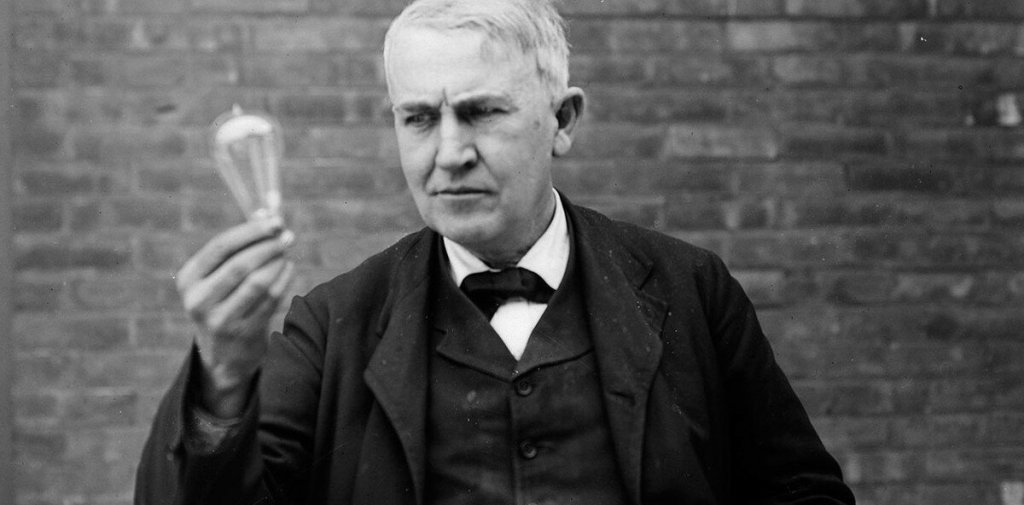 Edison holding incandescent bulb
