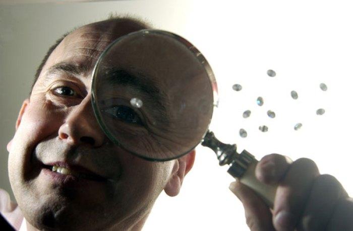 PR photo of jeweller Alistir Wood Tait inpecting fake diamonds