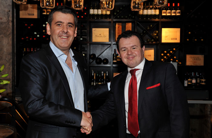 Attendees are seen shaking hands in a PR photgraph at the launch of Edinburgh wine bar, Divino Enoteca