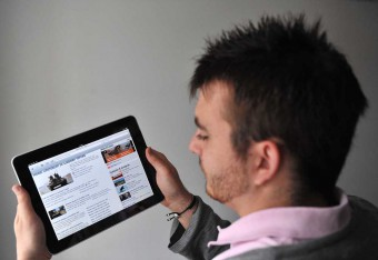 A young man using an iPad or similar tablet to shop online