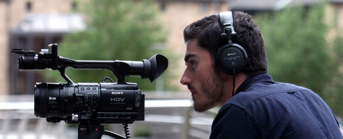 A video camera operator filming with a digital camera