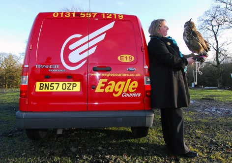 Ollie the Eagle Owl & handler leaning on the company van - Eagle couriers