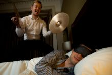 Hotel PR photography of guest sleeping in hotel quiet zone while man with cymbals attemps to wake him