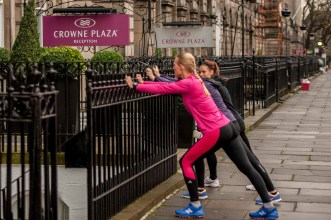 Crowne Plaza Hotel on Royal Terrace, Edinburgh, has a running station where guests, or visitors can plan a run around town. Hotel manager, and extreme runner, Lucja Leonard (in pink) takes two keen runners through their pre run stretch. (c) Wullie Marr/HOLYROOD For pic details, contact Wullie Marr........... 07989359845