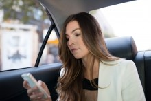 A female passenger using the Uber app in the back of an Uber car