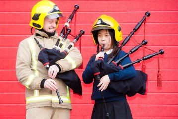 Firefighter and child with bagpipes
