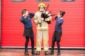 Firefigher with bagpipe and children covering ears