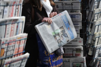 A woman buying a newspaper