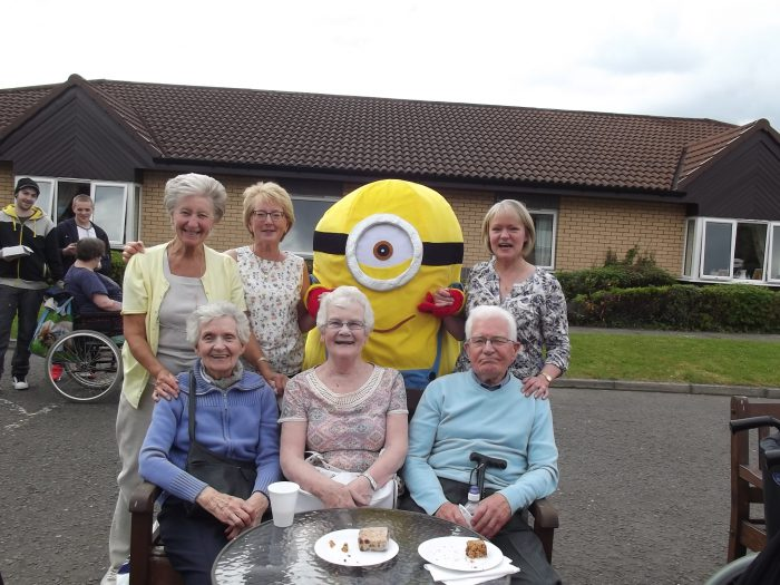 Elderly people enjoying Bupa care home Summer Fete