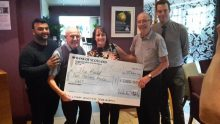 Five people dtand with a giant cheque for £2,000 by PR Experts in Edinburgh
