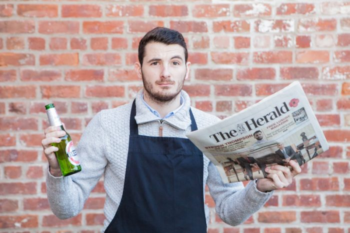 Man with beer in one hand and newspaper as he prepares for successful PR agency stint