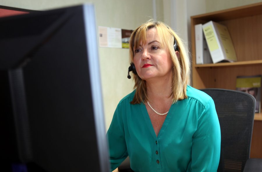 Woman sitting at computer wearing microphone head-set by PR Experts