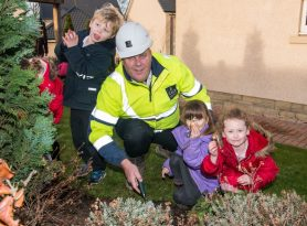 PR Photos of Three of the kids and CALA Site Manager Jim Murphy planting the daffodil bulbs