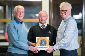 Site Manger Francis Cassidy presents the defib to Allan Murray Vice Chair of Currie Community council and Allister McKillop Chair of Currie Community Council