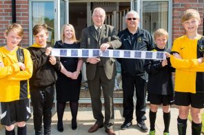 Councillor Ricky Henderson prepares to cut the ribbon to open Kinleith Mills showhomes alongside players from Currie F.C. captured by PR Photography