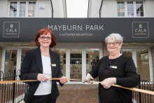An image of two ladies cutting the ribbon in front of the new Mayburn Park showhomes