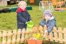 A photo of a young girl digging in a flower pot with a young boy who is watering the flower pot
