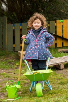 A picture of a young girl holding a rake standing in behind a wheelbarrow and a watering can