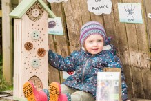 A picture of a young girl sat next to a bug hotel
