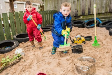 A photo of two young boys using their gardening tools in a sand pit