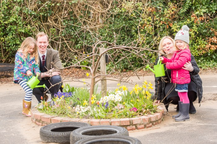 A photo of two young girls with a man and a woman watering a flower bed