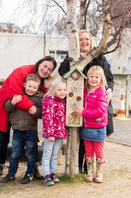 A photo of two young girls, a young boy and two women posing next to an insect house for Photography PR