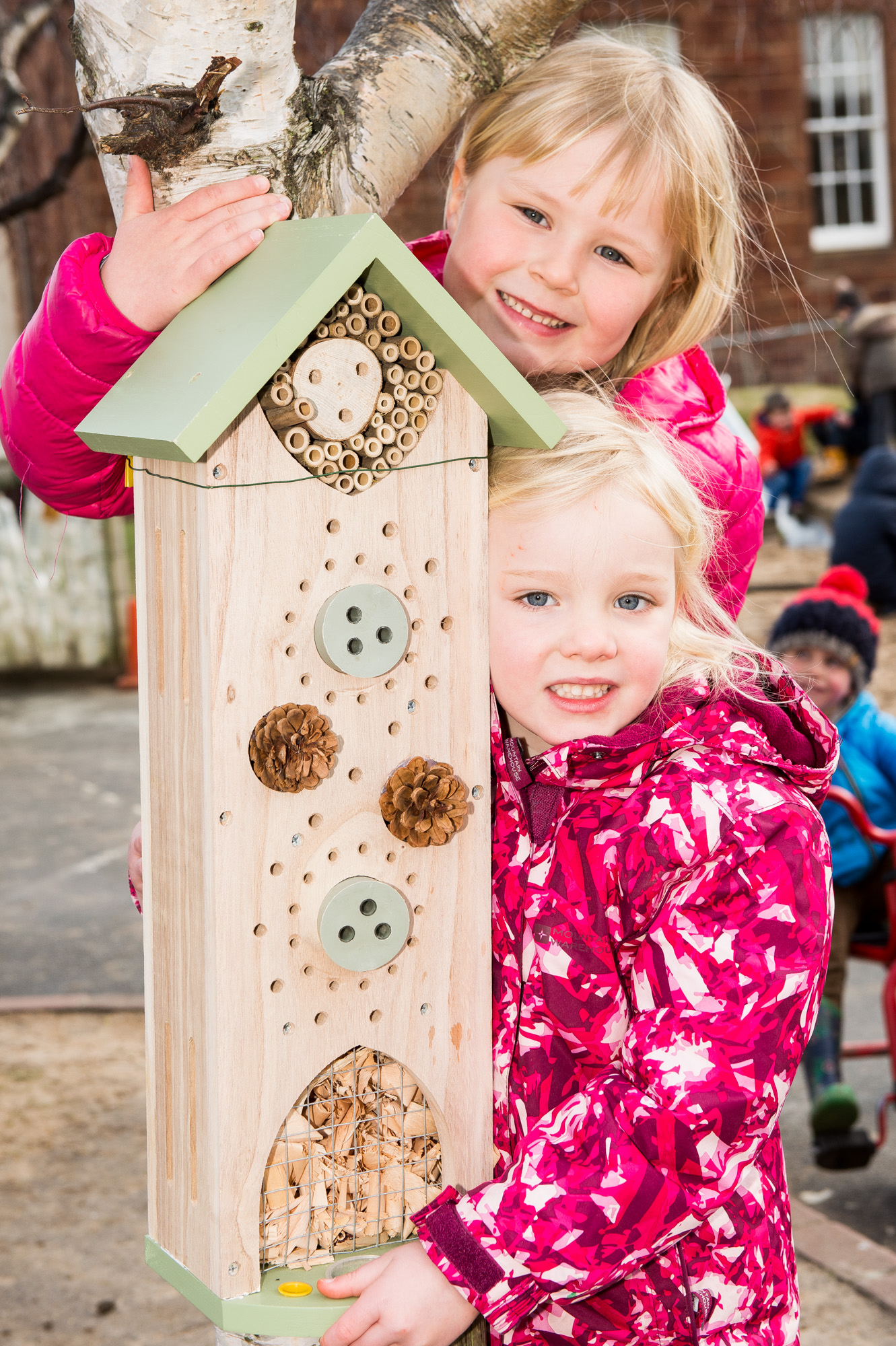 A photo of two young girls posing next to an insect house for Photography PR