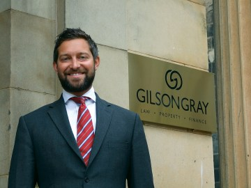 An image of Glen Gilson in a suit standing in front of Gilson Gray offices