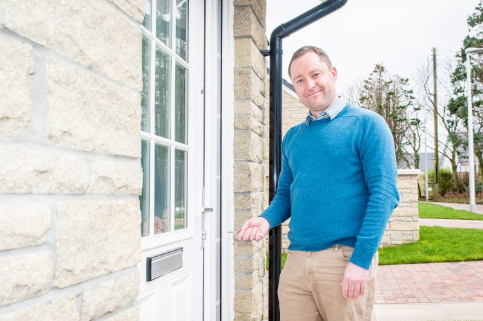 An image of Gordon Surfleet holding key in front of his new home as part of a Property PR photoshoot