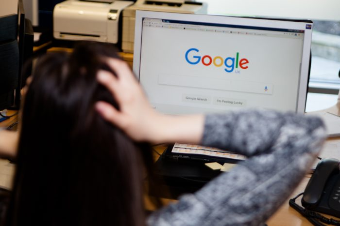 Person with head in hands looking at google as part of a digital pr story