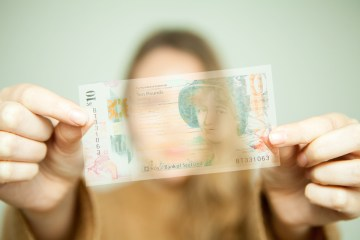 transparent money in front of blurred woman