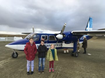 Public Sector PR photograph of Fair Isle school children Grace Parnaby, 9 Freyja Parnaby, 6, and Lewis Wright-Stanners, 9 in front of a light aircraft