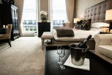 Hotel PR photograph of a bottle of champage and two glasses in a romantic bedroom at Nira Caledonia hotel in Edinburgh