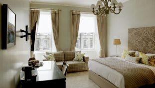 Hotel PR photograph of an elegant, bright bedroom at Nira Caledonia