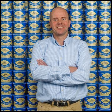 Mac Mackie is pictured infront of a wall of Mackie's traditional ice cream tubs