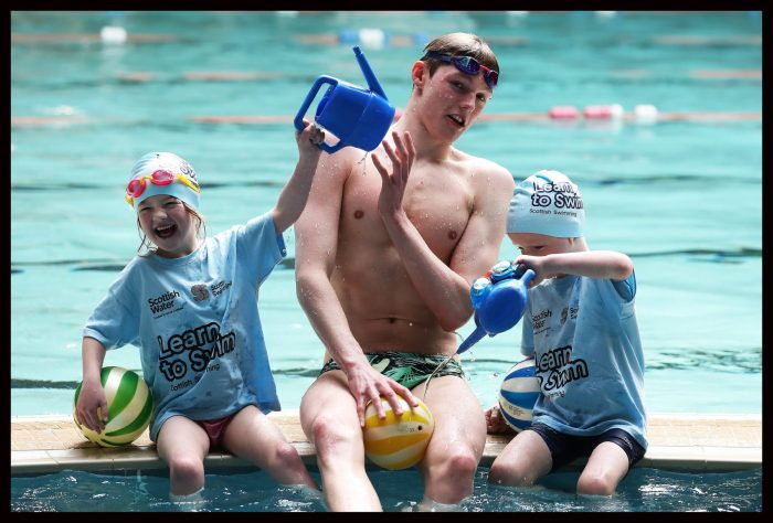 Public Sector PR photo of Learn to Swim Ambassador Duncan Scott sat at the edge of a pool with two children pouring water over his head at Teviotdale Leisure Centre